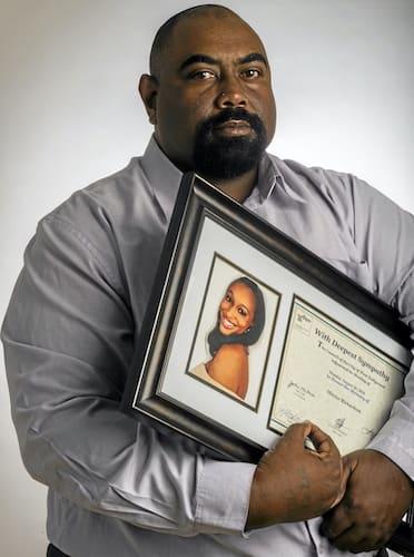 michael richardson holding a photo of mitrice